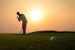 Golf ball that is about to hole together with the golfer hold a putter and lift up fist in background amid the golden sky of the evening sun.
