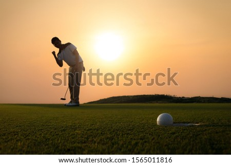 Golf ball that is about to hole together with the golfer hold a putter and lift up fist in background amid the golden sky of the evening sun. Foto stock ©