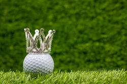 Golf ball with crown on green grass background. The
