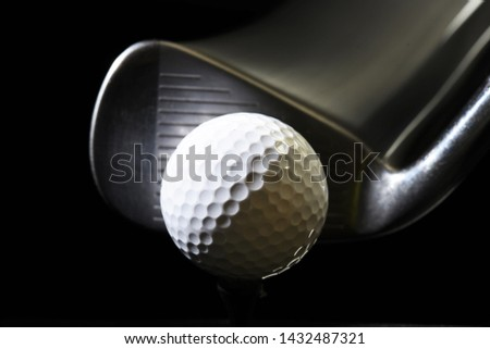 golf ball with iron club head in moment of teeing off on black background