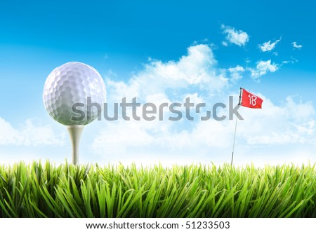 Golf ball with tee in the grass against blue sky