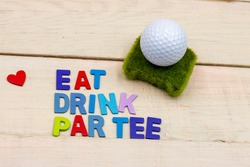 Golf ball with word eat drink par tee for golf party concept on wooden background