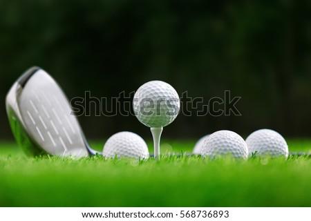 Golf balls and golf club on green grass