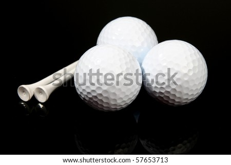 Golf balls and tees on black
