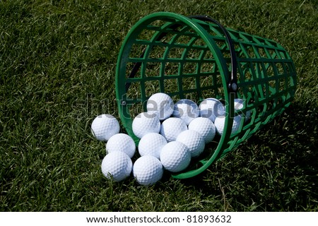 golf balls in a basket on the green grass