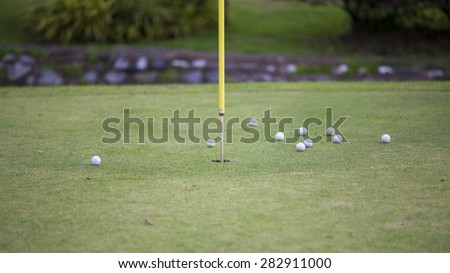 Golf balls in practice hole with flag marking the hole