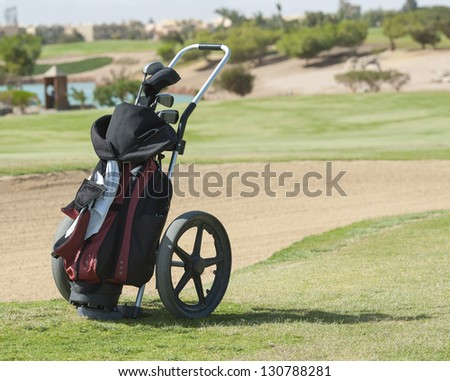 Golf caddy trolley and bag on a golf course with bunker in the background