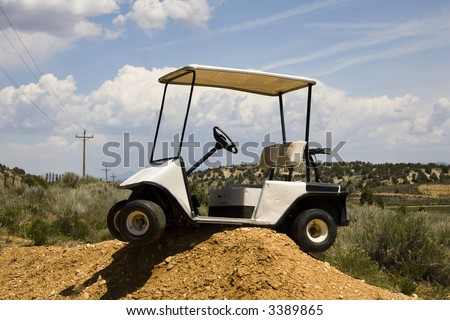 Golf cart high centered on a dirt mound