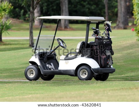 Golf cart loaded with clubs on a course.