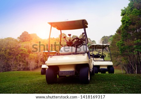Golf cart on fairway in golf course and beautiful fairway and layout. Tree around fairway on field meadow on mountain.