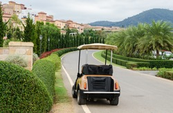 Golf cart or club car park on the way to modern village.