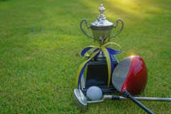 Golf champion trophy on green grass with golf clubs and golf ball in beautiful golf course. Sports that people around the world play during the holidays for health.