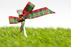 Golf Christmas Holiday with golf ball and Christmas ribbon on green grass