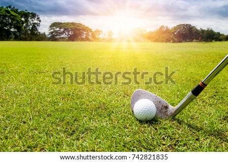 Golf club and golf ball in grass in sunrise. #742821835