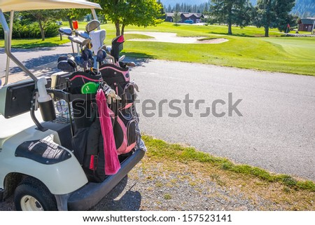 Golf Club Bags on back of cart. Golf course with sand trap in background. Copy space.
