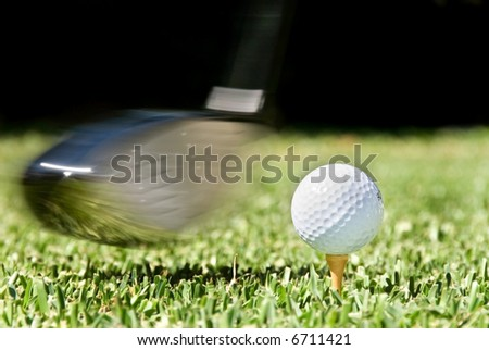 Golf club being swung at golf ball during a competition