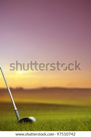 golf club hitting golf ball along fairway at sunset