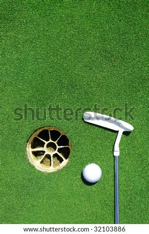 Golf club, hole, white ball on green grass with room for copy space