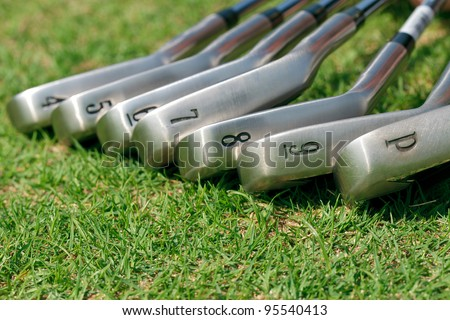 Golf club laying on green grass