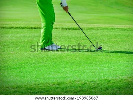 Golf club. Man playing golf Green golf field and ball in grass