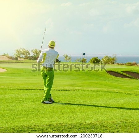 Golf club. Man playing golf Green golf field and ball in grass