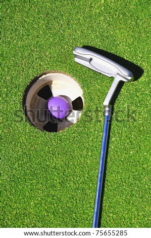 Golf club with ball in hole