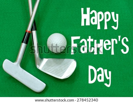 Golf clubs and golf ball on green felt background. Happy Father\'s Day message in white on the green felt. Clubs are a putter and a wedge, crossed, with a golf ball positioned above.  Horizontal image