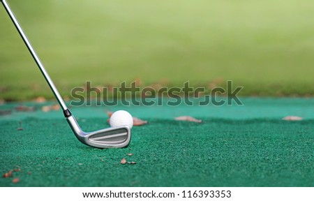 Golf clubs and golf balls on a green background