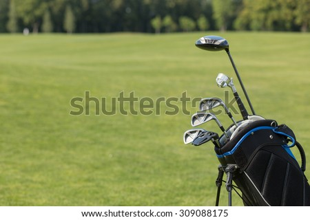 Golf clubs over green field background. Bunch of golf clubs in the bag ready to be used for playing professional golf and having nice vacation in summer.