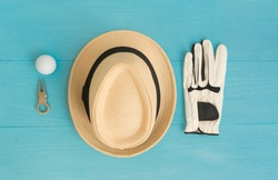Golf concept : panama hat, glove, golf balls, divot repair tool on wooden table. Flat lay with copy space.