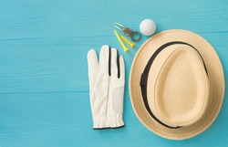 Golf concept : panama hat, glove, golf balls, golf tees, divot repair tool on wooden table. Flat lay with copy space.