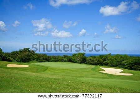 Golf course against deep blue sky with clouds and sand pools under white puffy clouds and the caribbean sun in tropical barbados in the western corner of the island - stock photo