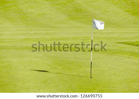 Golf course hole and flag blowing on a sunny day