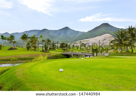 Golf course in luxury resort. Golf green field on the background of the mountains and beautiful palm tree over blue sky with white clouds view