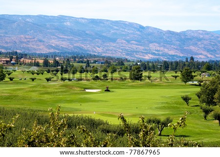 Golf course in the Okanagan valley set among vineyards and apple orchards with a backdrop of lake Okanagan