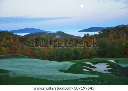 golf course nestled in the North Carolina mountains in the Fall just as the morning fog lifts in the valleys