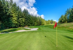 Golf course with gorgeous green, sand bunker and golf flag and real estate on background.
