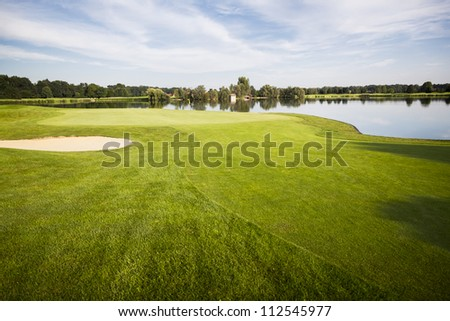 Golf course with green, sand trap and lake with cloudscape in background.