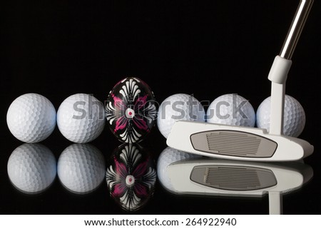 Golf equipments and egg on a black glass desk