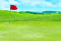 Golf field. Green grass against the background of the sea shore and the blue sky. Signal flag for the hole on the golf course