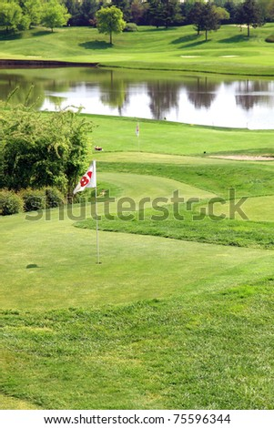 golf field with flag and artificial lake in background