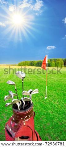 Golf game. Golf clubs in bag against the golf course with bright sun.