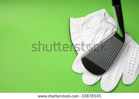 Golf glove and club on a green background