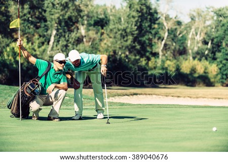 Golf. Golfer reading the green with his caddy Foto stock ©