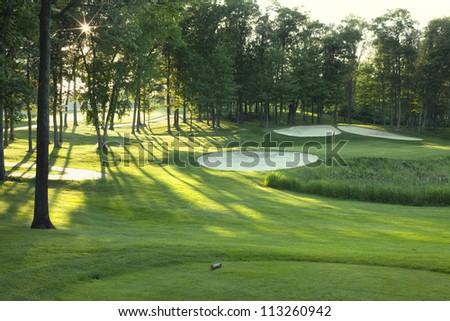 Golf green and traps with rays of sun