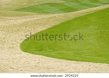 Golf green next to rough on a golf course.