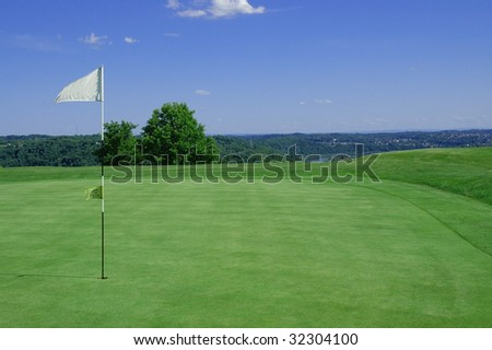 Golf green with flag blowing in wind room for copy space