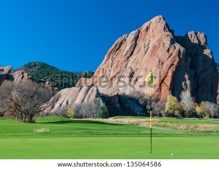Golf green with flagstick and ball with a dramatic rocky background and blue sky