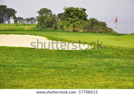 Golf green with sand trap and red flag