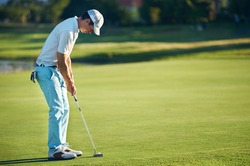 Golf man putting on green for birdie while on vacation